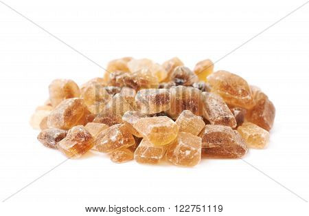 Pile of brown rock sugar crystals isolated over the white background, side view foreshortening