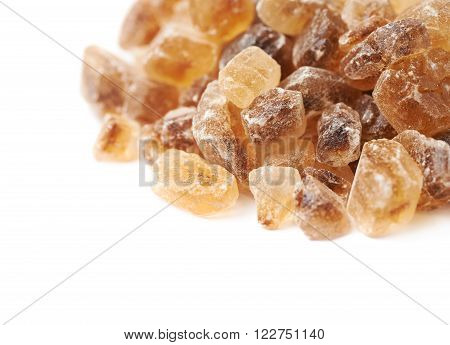 Pile of brown rock sugar crystals isolated over the white background, close-up crop composition
