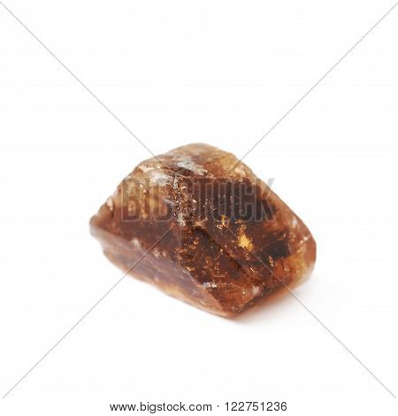 Single large dark brown rock sugar crystal isolated over the white background