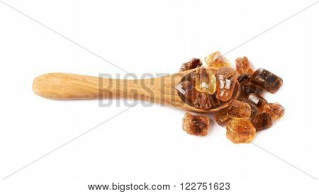 Wooden spoon full of large brown rock sugar crystals isolated over the white background, top view above