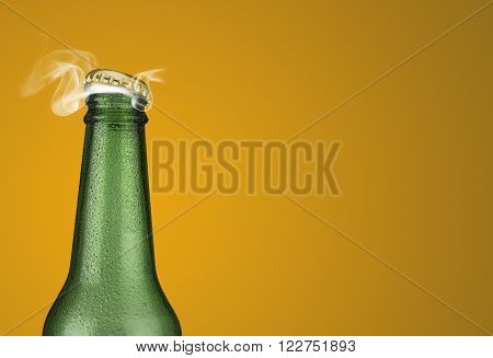 Horizontal photo of a green cold beer bottle with water drops and golden cap open on yellow background