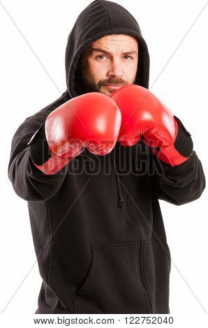 Amateur boxer wearing a black hoodie and red box gloves in the fighting position isolated on white background