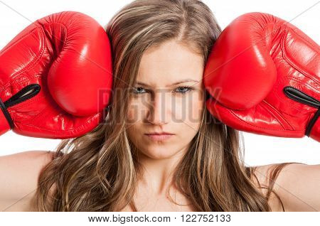Portrait of a beautiful female model with boxing gloves and serious angry or mad face