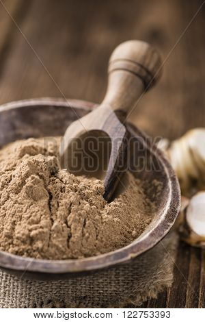 Galangal Powder on wooden background (detailed close-up shot)