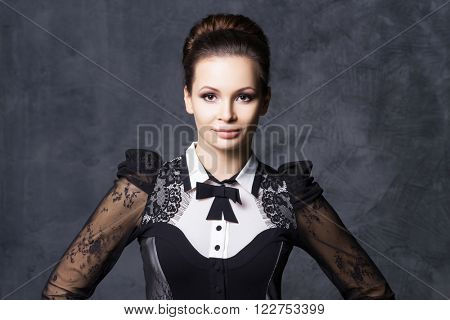 Portrait of beautiful and young woman in fashion dress with a bow tie.