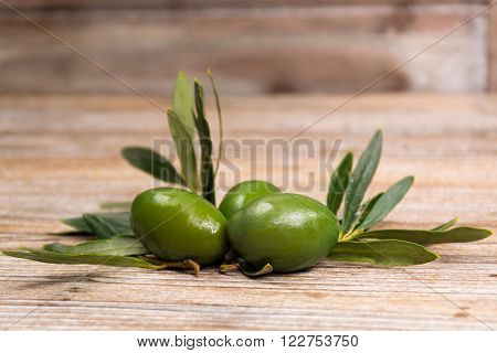 Giant green olives with leaves on wooden background