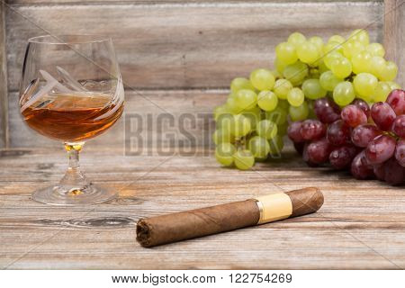 Cigar and amber color brandy with green and red fresh grape on wooden backdround