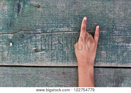 a hand making a rude gesture or good wishes on aged wooden background
