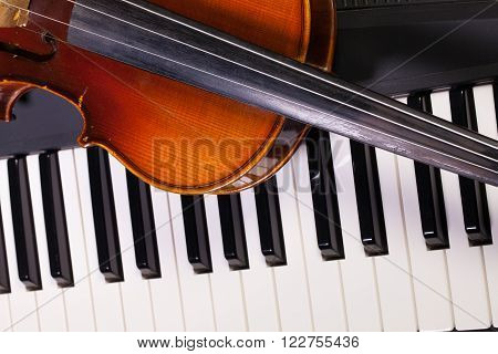 Detail of piano keyboard and old violin