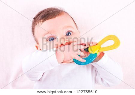 Beautiful baby girl with rattle teether toy.
