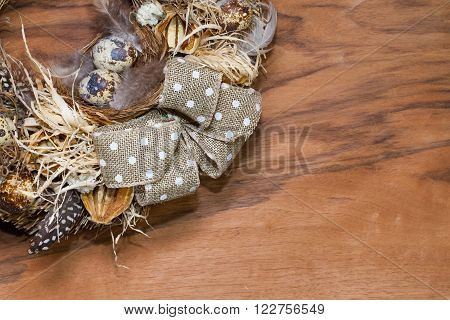 Easter wreath with dry grasspine cones feathers quail eggs and brown bow on the wooden table