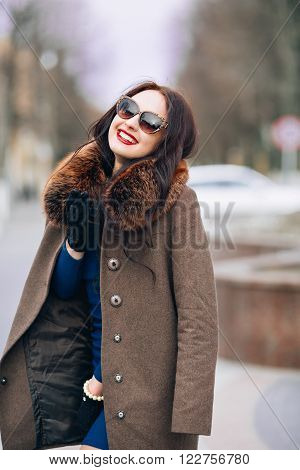 Beautiful Woman in Luxury Fur Coat. Stylish brunette woman in brown coat. young sexy sensual seductive woman with perfect fluffy curled hairs, amazing smile with brilliant white teet, vintage sunglasses..