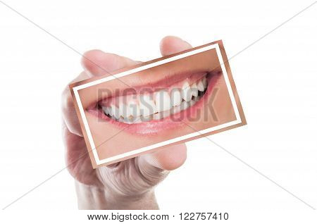 Hand holding a card with perfect woman smile denture or teeth isolated on white background