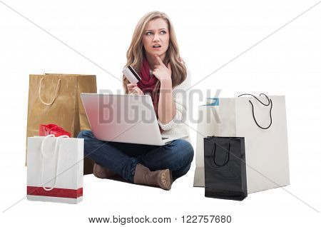 Worried shopping woman holding card and thinking what else to buy online using laptop