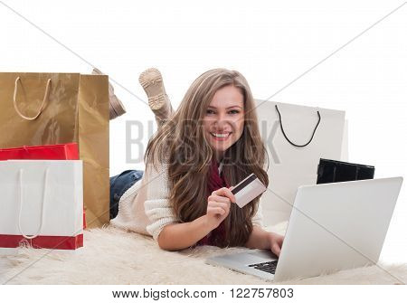 Happy and satisfied shopping girl using laptop and holdinf credit or debit card surrounded by shopping bags
