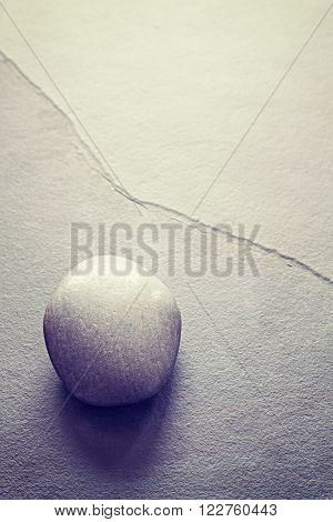 Vintage toned rounded stone on a slate, abstract natural background with copy space.