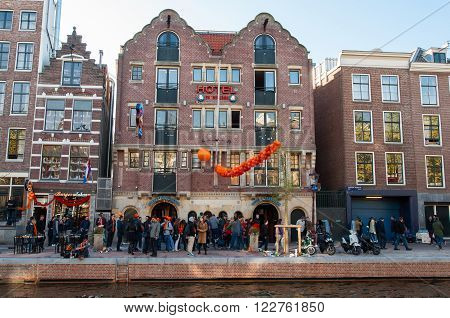 AMSTERDAM-APRIL 27: Famous Amsterdam Bulldog coffeeshop and hotel in red-light district people celebrate King's Day outside the cafe on April 272015 the Netherlands.