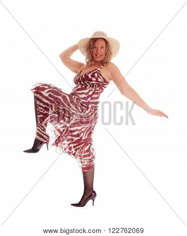 A middle age woman in a summer dress and straw hat dancing isolated 