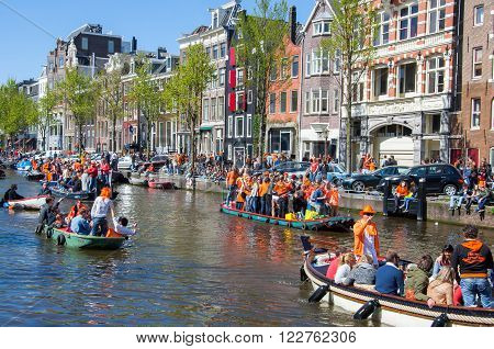 AMSTERDAM-APRIL 27: Party Boat with crowd of people along the canal on King's Day on April 272015 the Netherlands. King's Day is the largest open-air festivity in Amsterdam.