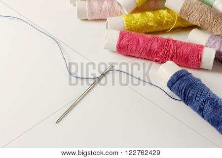 Multicolored bobbins of thread and needle on white