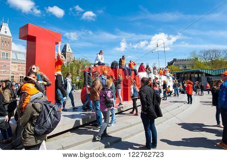 AMSTERDAM-APRIL 27: Tourists take picture in front of red and white letters the 'I amsterdam' next to the Rijksmuseum during King's Day on April 27 2015 the Netherlands.