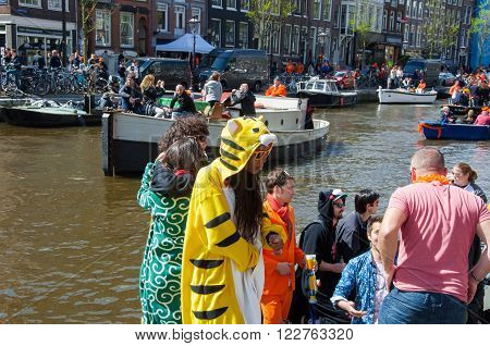 AMSTERDAM-APRIL 27: Locals and tourists solemnize King's Day along the Singel canal on April 272015. King's Day is the largest open-air festivity in Amsterdam.