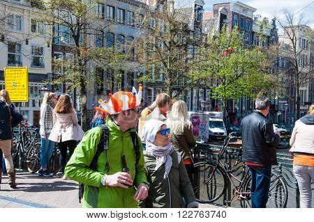 AMSTERDAM-APRIL 27: Locals and tourists in orange celebrate Koningsdag (King's Day) on April 272015 the Netherlands. King's Day is the largest open-air festivity in Amsterdam.