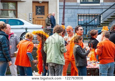 AMSTERDAM-APRIL 27: Locals in orange take part at celebration Koningsdag (King's Day) on April 272015 the Netherlands. King's Day is the largest open-air festivity in Amsterdam.