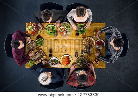 Top view creative photo of friends sitting at wooden vintage table. Friends of six having dinner. They with plates full of meal and glasses with drinks. There is free space in the middle of table