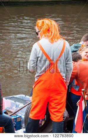 AMSTERDAM-APRIL 27: Undefined person in traditional orange on a boat during King's Day on April 272015. Orange is the color of the Dutch royal family dating back to William of Orange.