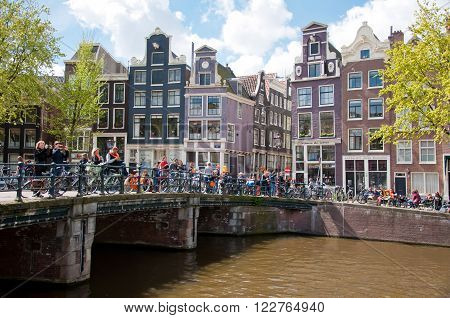 AMSTERDAM-APRIL 27: King's Day boating through Amsterdam canals people have fun on the bridge on April 27 2015. King's Day (Koningsdag) is held on 27 April (the king's birthday) every year.