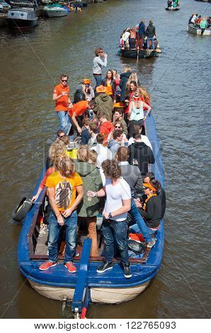 AMSTERDAM - APRIL 27: Local people on Party Boat with unlimited beer celebrate King's Day on April 27, 2015. King's Day is the largest open-air festivity in Amsterdam.