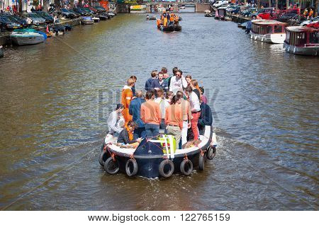 AMSTERDAM, NETHERLANDS - APRIL 27: Boat party along Amsterdam's canals during King's Day on April 27, 2015. King's Day is the largest open-air festivity in Amsterdam the Netherlands.