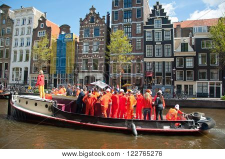 AMSTERDAM, NETHERLANDS - APRIL 27: Boat party with DJ on a boat Amsterdam canal during King's Day on April 27, 2015. King's Day is the largest open-air festivity in Amsterdam the Netherlands.