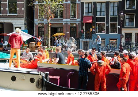 AMSTERDAM, NETHERLANDS - APRIL 27: Boat party on Amsterdam canal during King's Day on April 27, 2015 in Amsterdam. King's Day is the largest open-air festivity in Amsterdam.
