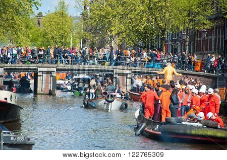 AMSTERDAM, NETHERLANDS - APRIL 27: Boat party through Amsterdam canals with unlimited beer during King's Day on April 27, 2015. King's Day is the largest open-air festivity in Amsterdam the Netherlands.