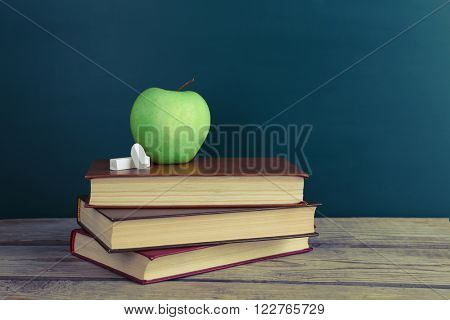 Few books with green apple and chalk on table