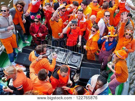 AMSTERDAMNETHERLANDS-APRIL 27: People in orange clothes during King's Day on a boat on April 272015 in Amsterdam. King's Day is the largest open-air festivity in Amsterdam.