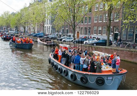 AMSTERDAMNETHERLANDS-APRIL 27: Boat party during King's Day on April 272015 in Amsterdam. King's Day is the largest open-air festivity in Amsterdam.