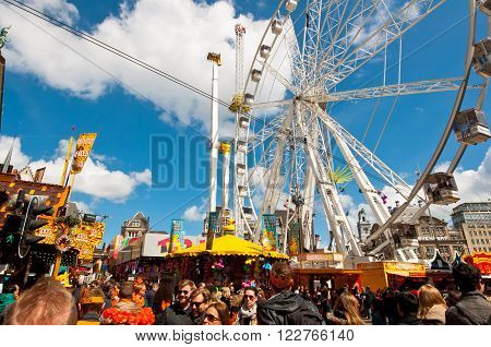 AMSTERDAM, NETHERLANDS-APRIL 27: King's Day on Dam Square with amusement park and people dressed in orange on April 272015 in Amsterdam. King's Day is the largest open-air festivity in Amsterdam.