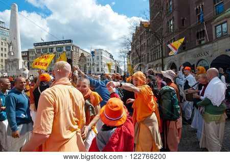 AMSTERDAM, NETHERLANDS-APRIL 27: Locals in traditional orange clothes on Dam during King's Day on April 272015 in Amsterdam. King's Day is the largest open-air festivity in Amsterdam.