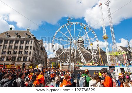 AMSTERDAMNETHERLANDS-APRIL 27: Locals and tourists dressed in orange on King's Day on April 272015. King's Day is the largest open-air festivity in Amsterdam.