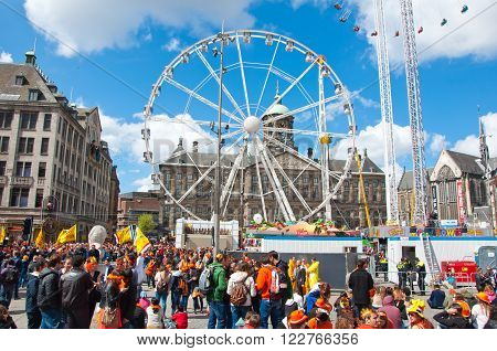 AMSTERDAM - APRIL 27: Dam Square with Ferris wheel and Royal Palace on the background during King's Day on April 27, 2015 in Amsterdam. King's Day is a national holiday celebrated on April 27th.