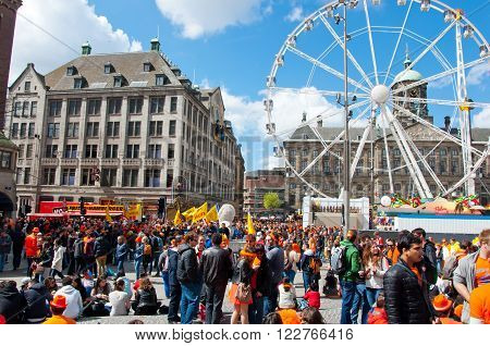 AMSTERDAM-APRIL 27: Crowd of people on Dam Square and Royal Palace on the background during King's Day on April 27 2015 in Amsterdam. King's Day is a national holiday celebrated on April 27th.