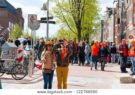 AMSTERDAMNETHERLANDS-APRIL 27: Young couple in orange take picture around red light district on King's Day on April 2727 in Amsterdam. King's Day is the largest open-air festivity in Amsterdam.