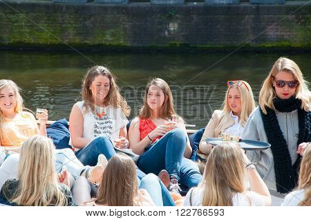 AMSTERDAMNETHERLANDS-APRIL 27: Local girls celebrate King's Day in a boat on April 272015 in Amsterdam. King's Day is the largest open-air festivity in Amsterdam.
