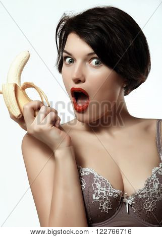 beautiful and sexy brunette with a banana in his hand green eyes