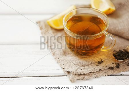 Glass cup of green tea with sliced lemon on wooden table with sackcloth closeup