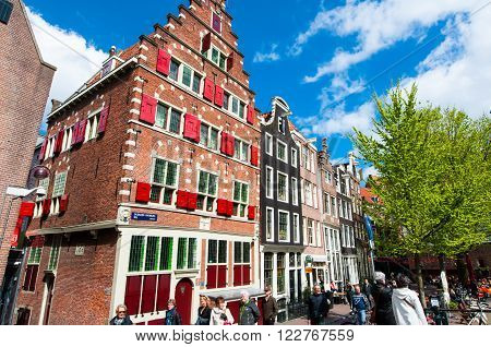 Amsterdam-April 27: Red-light district architecture people go sightseeing on April 272015 the Netherlands. King's Day is the largest open-air festivity in Amsterdam.