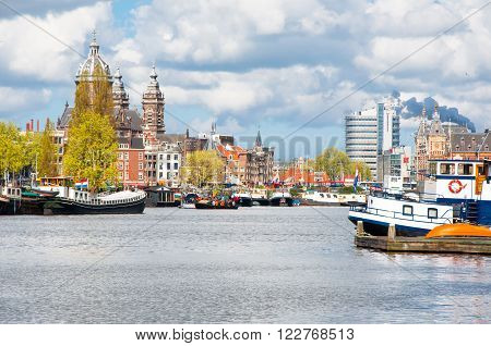 Amsterdam cityscape with St. Nicolas church and Schreierstoren (Weeper's Tower) in the background.